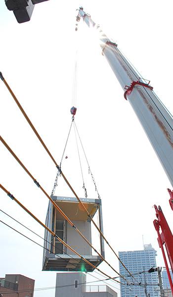 クレーンに吊られたユニットが電線を越える